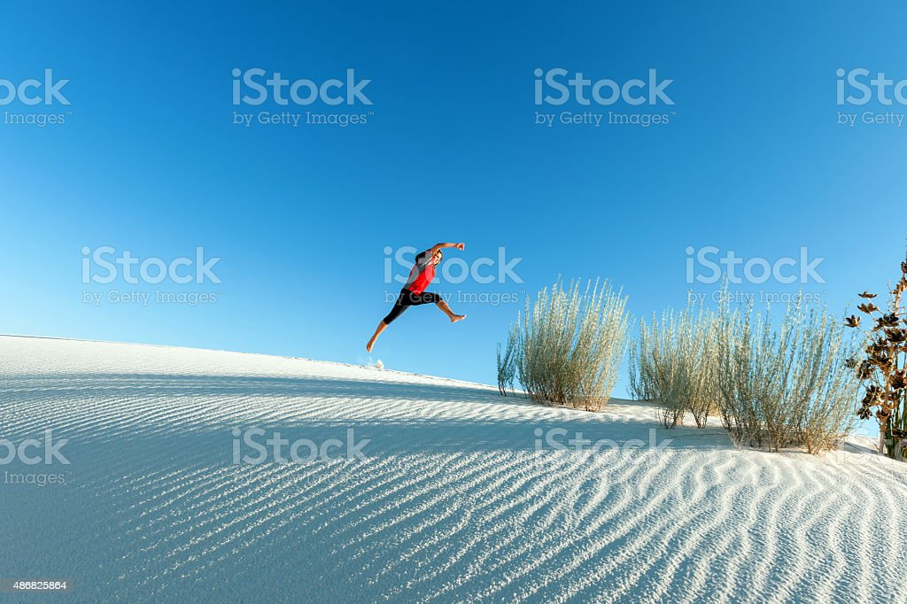 Young Woman Jumping in White Sands National Monument USA stock photo