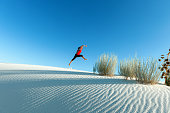 Young Woman Jumping in White Sands National Monument USA