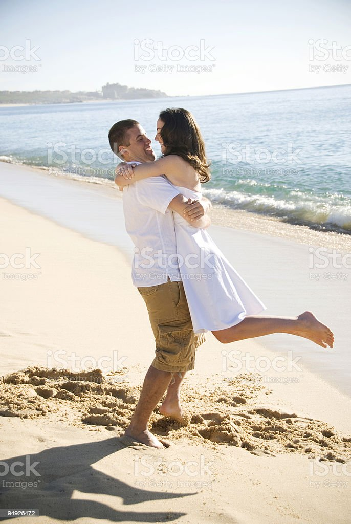 A young woman jumping into her boyfriend's arms on the beach royalty-free stock photo