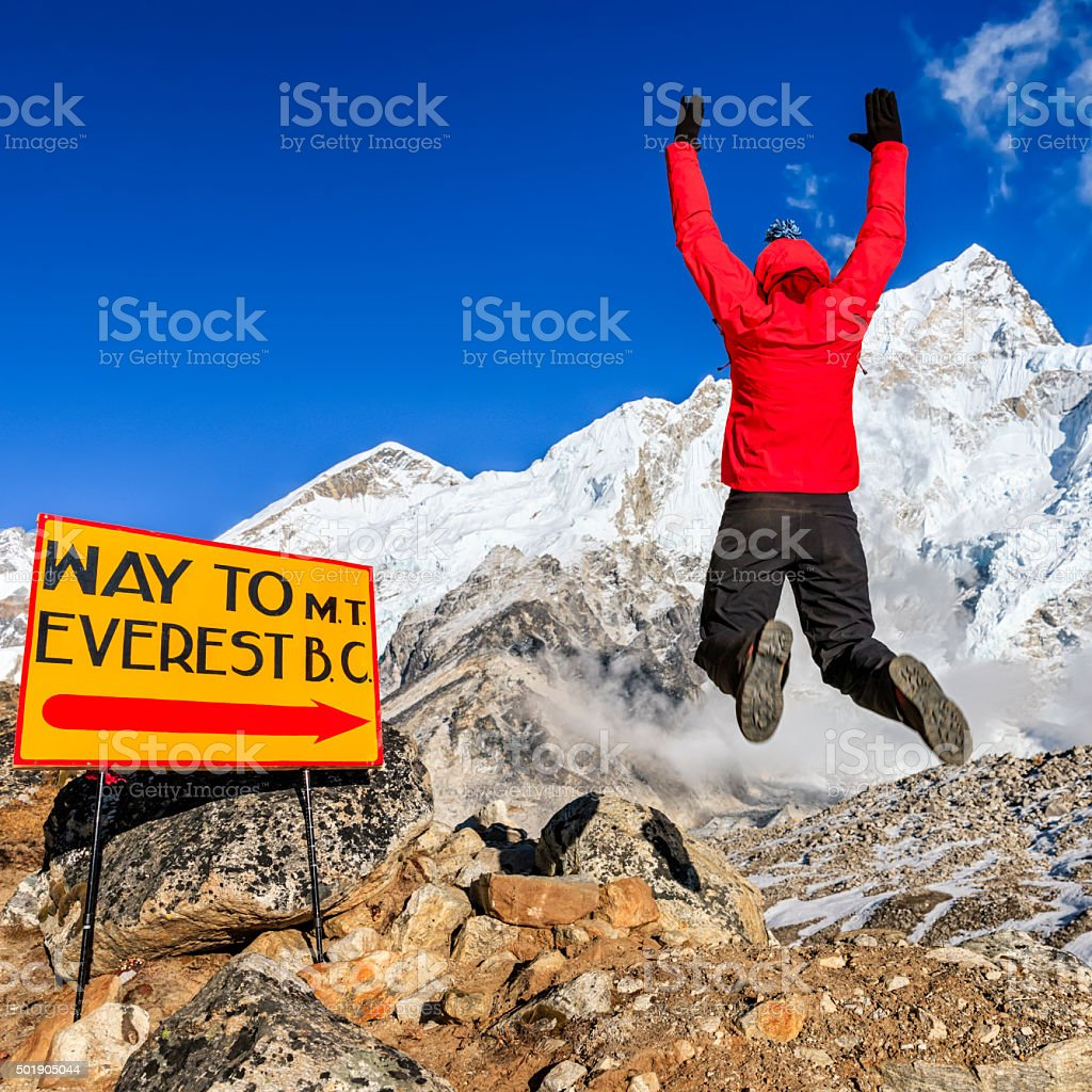 Young woman jumping next to signpost 'Way to MountEverest BaseCamp' stock photo