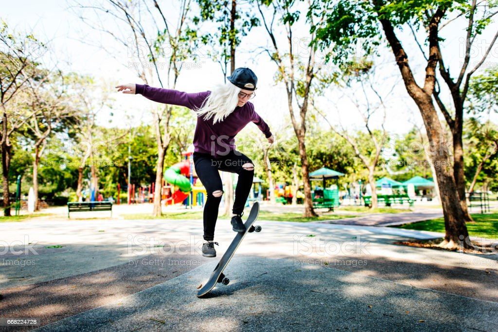 Young Woman Jumping Olly Skateboard Concept stock photo
