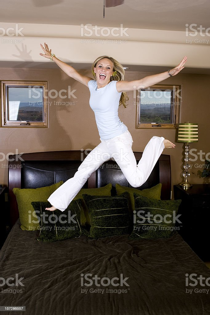 Young Woman Jumping on Bed stock photo