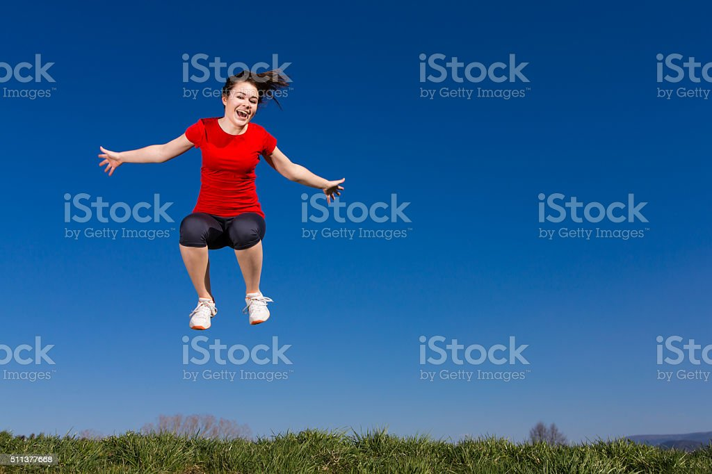 Young woman jumping outdoor stock photo