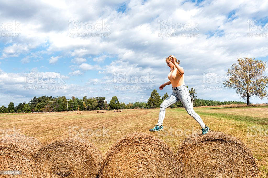 Young woman jumping over hay roll bales stock photo