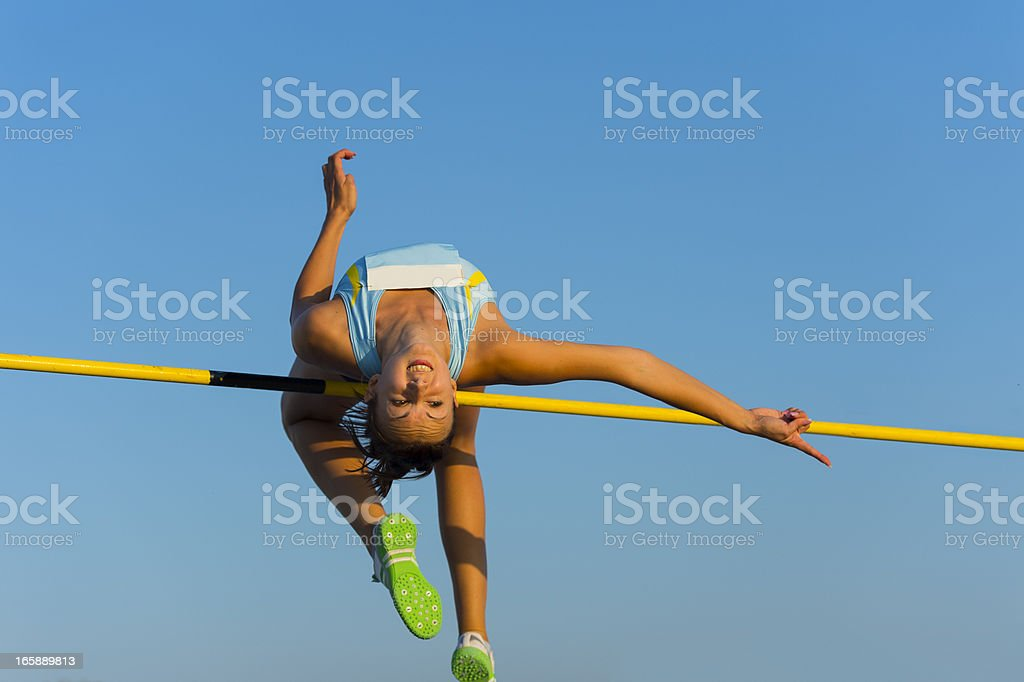 Young woman jumping over the lath during competition stock photo