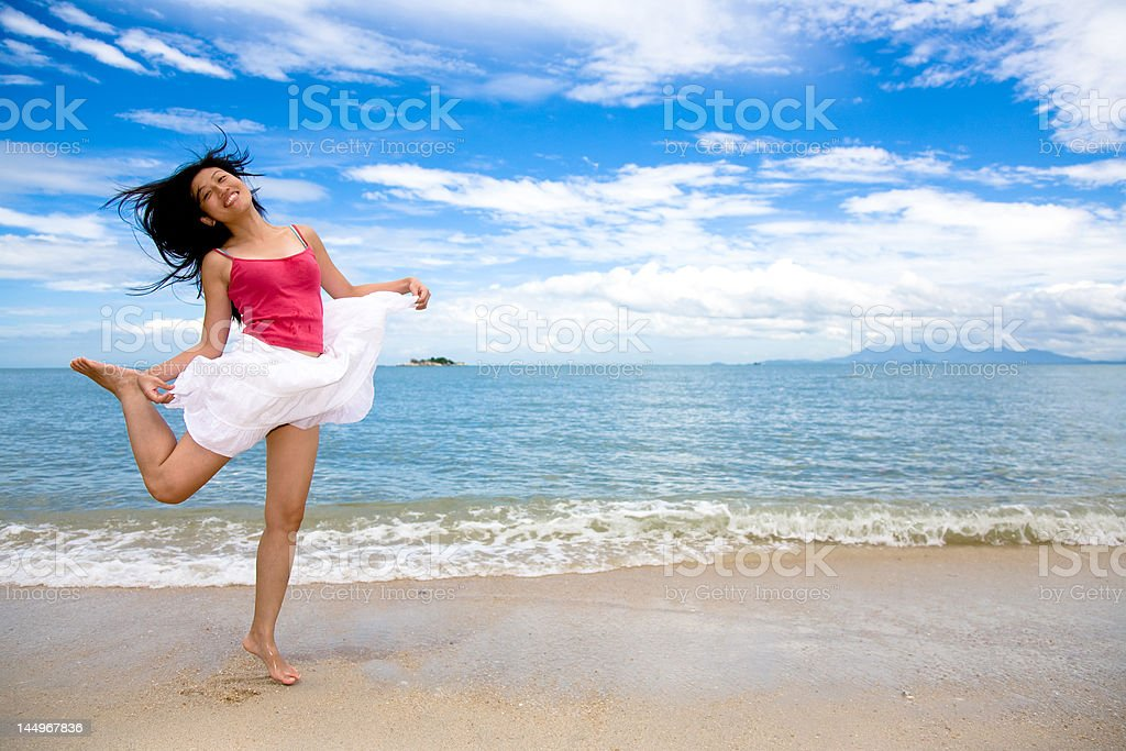 young woman jumping playfully at the beach royalty-free stock photo