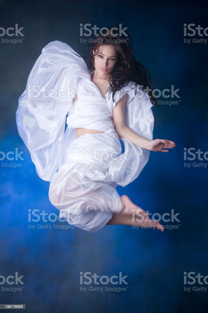 Young Woman Jumping Wearing White Sheet Toga stock photo