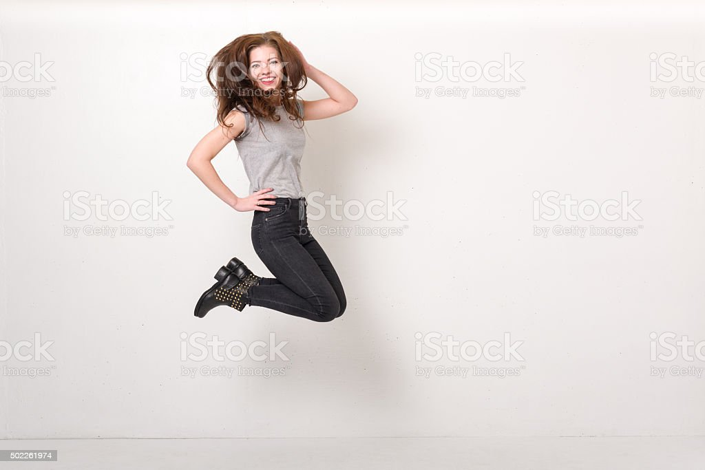 Young woman jumping with a textured white wall background stock photo