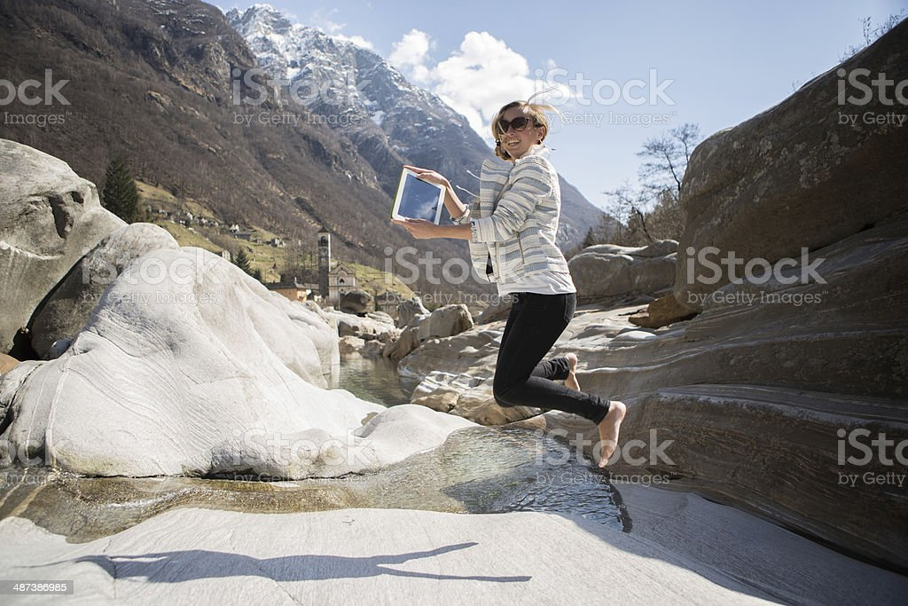 Young woman jumping with digital tablet royalty-free stock photo