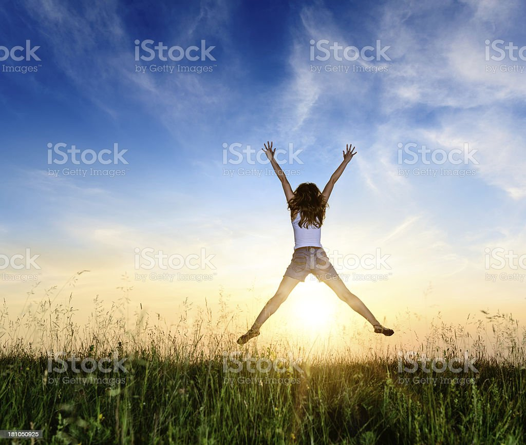 Young woman jumping with joy in meadow stock photo