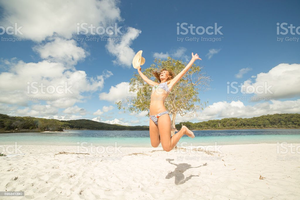 Young woman jumps high up in the air on beach stock photo
