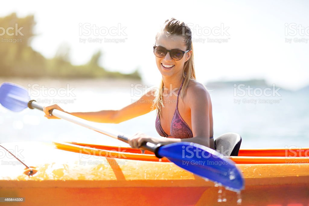 Young woman kayaking during summer day. stock photo