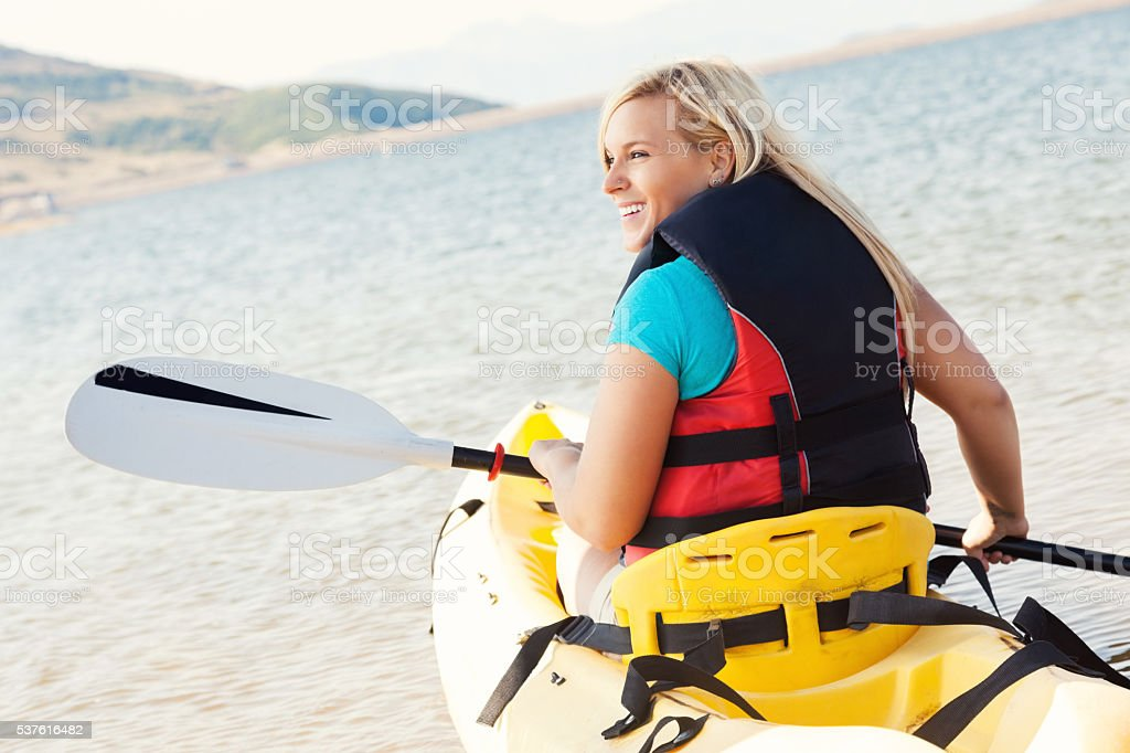 Young woman kayaks on a mountain lake stock photo