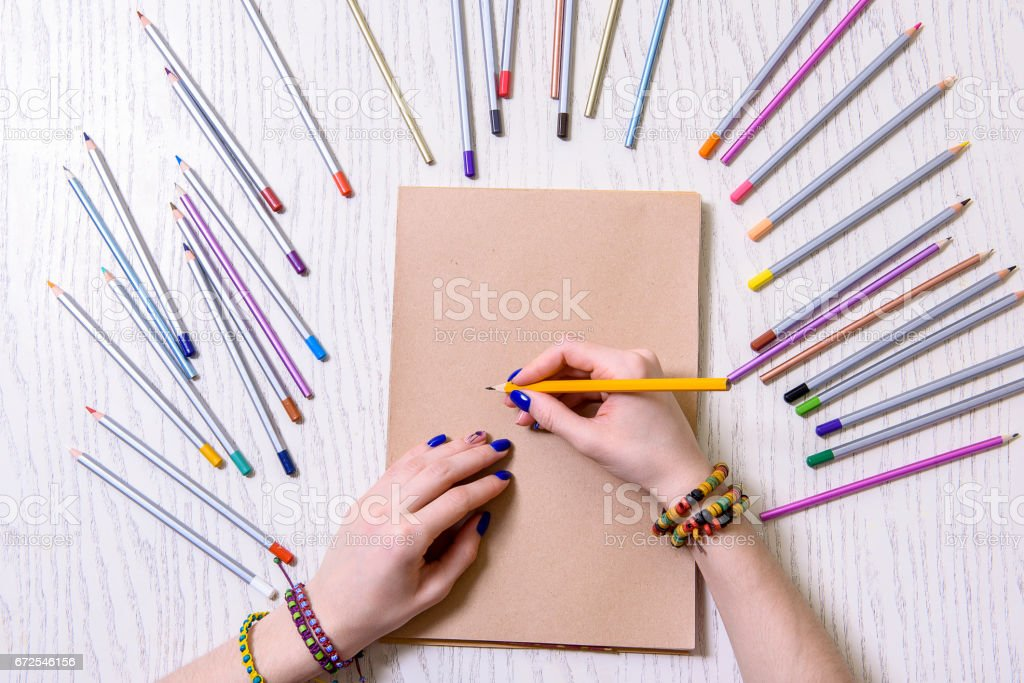 Young woman keeping orange pencil stock photo