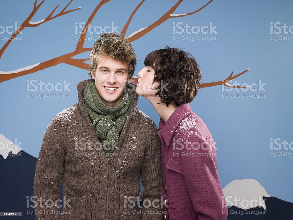 Young woman kissing boyfriend stock photo