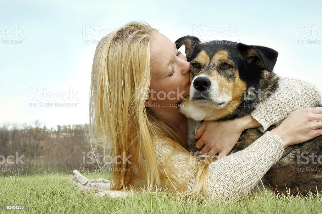 Young Woman Kissing German Shepherd Dog Outside stock photo
