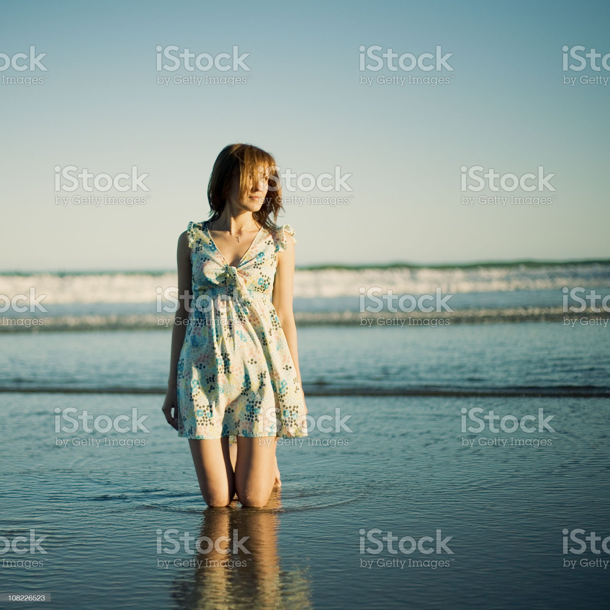 Young Woman Kneeling on Beach royalty-free stock photo