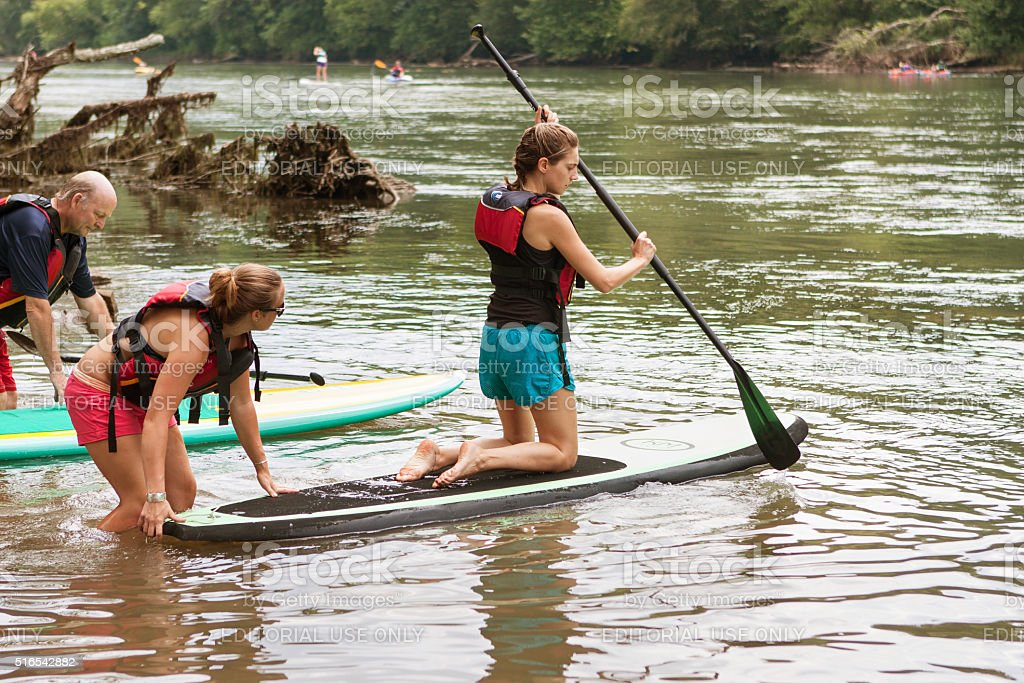 Young Woman Kneels On Paddleboard In Chattahoochee River stock photo