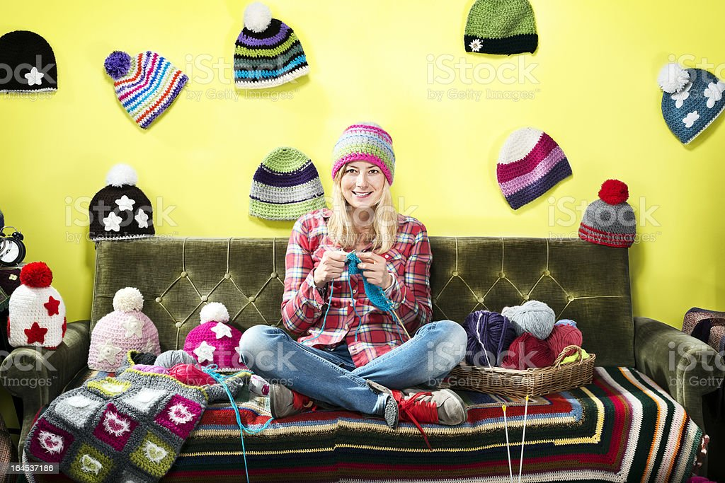 Young woman knitter portrait on couch with winter hats stock photo