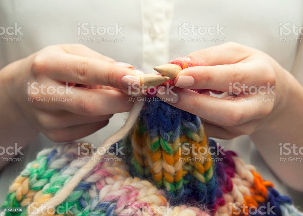 Young woman knitting a woolen colorful scarf, closeup stock photo