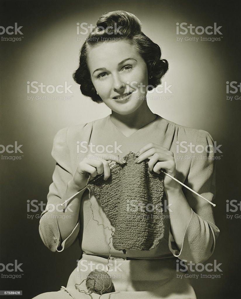 Young woman knitting in studio, (B&W), portrait stock photo