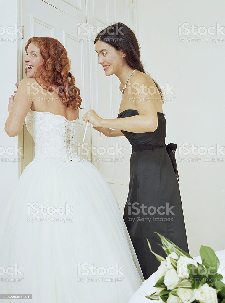 Young woman lacing up bride's dress, smiling stock photo