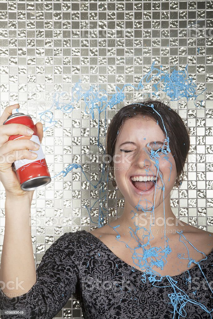 Young woman laughing and spraying party string over herself stock photo