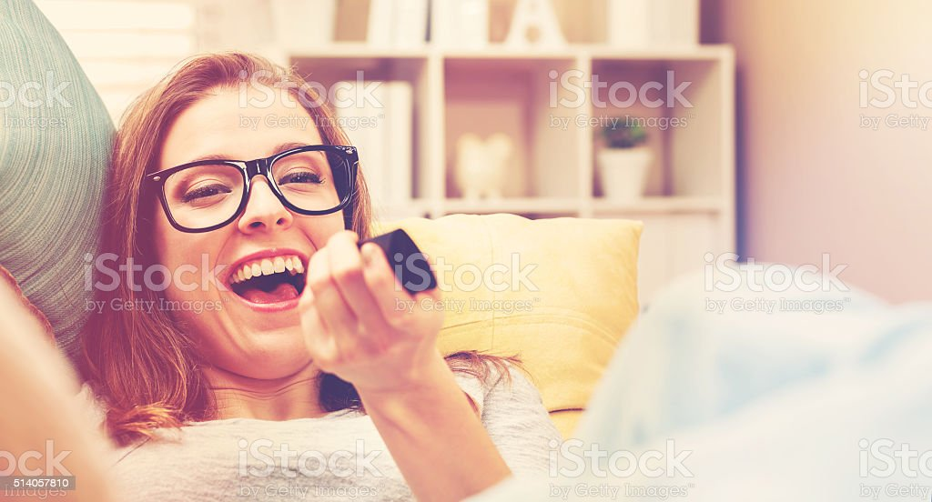 Young woman laughing while watching TV stock photo