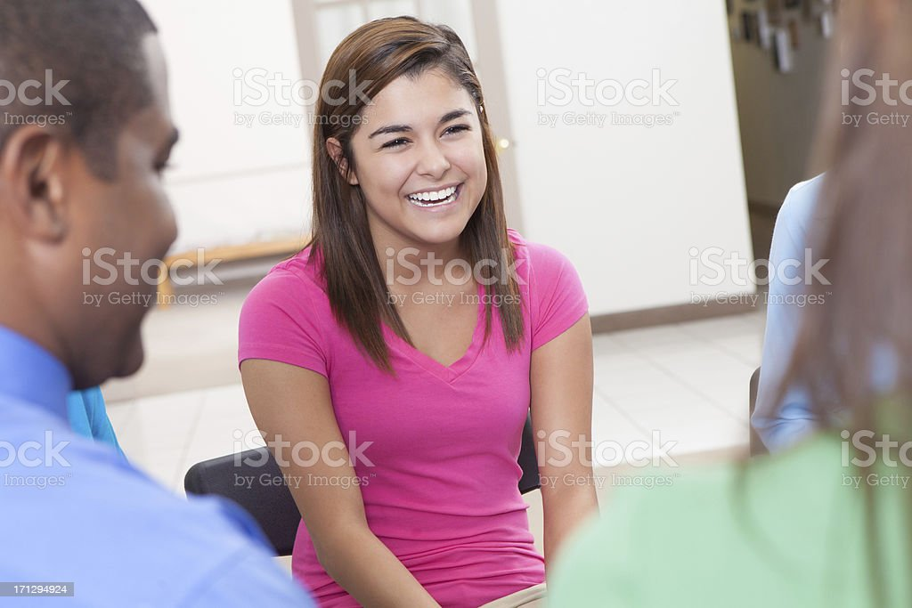 Young woman laughing with friends in a group discussion royalty-free stock photo