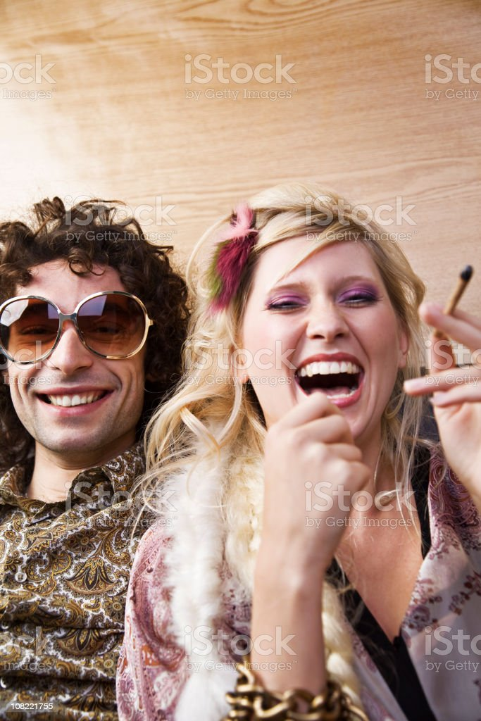 Young Woman Laughing with Hippie Man Smoking Marijuana royalty-free stock photo