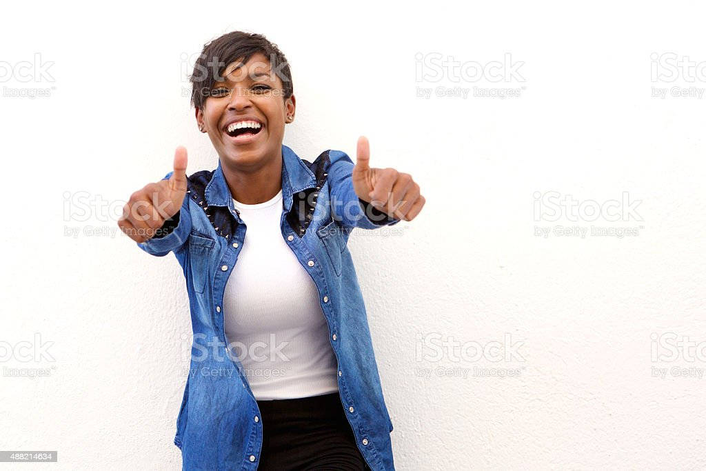 Young woman laughing with thumbs up sign stock photo