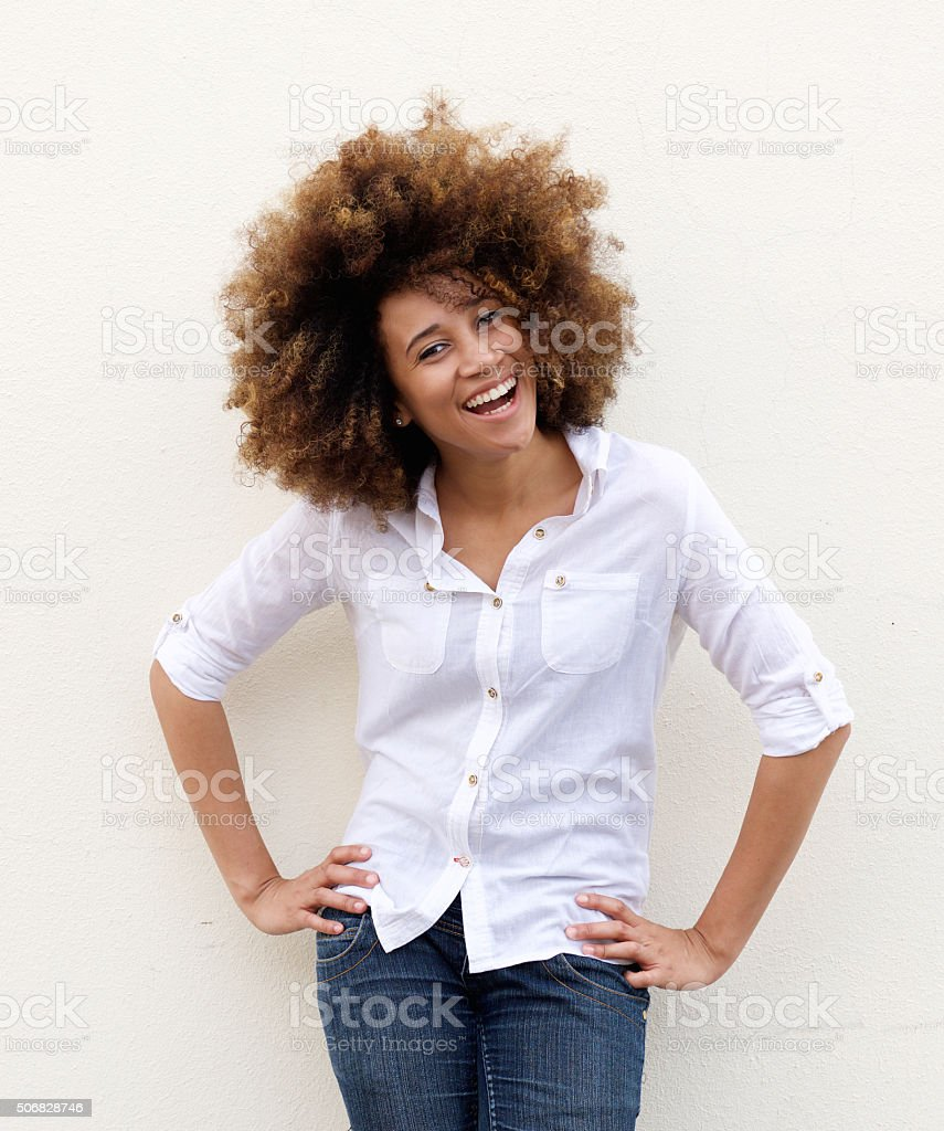 Portrait of a young woman laughing with white shirt ad afro hair