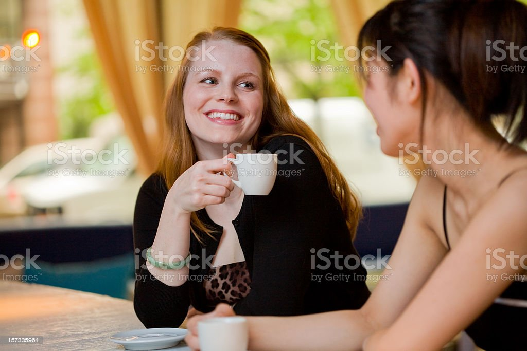 Young woman laughs with friend drinking coffee royalty-free stock photo