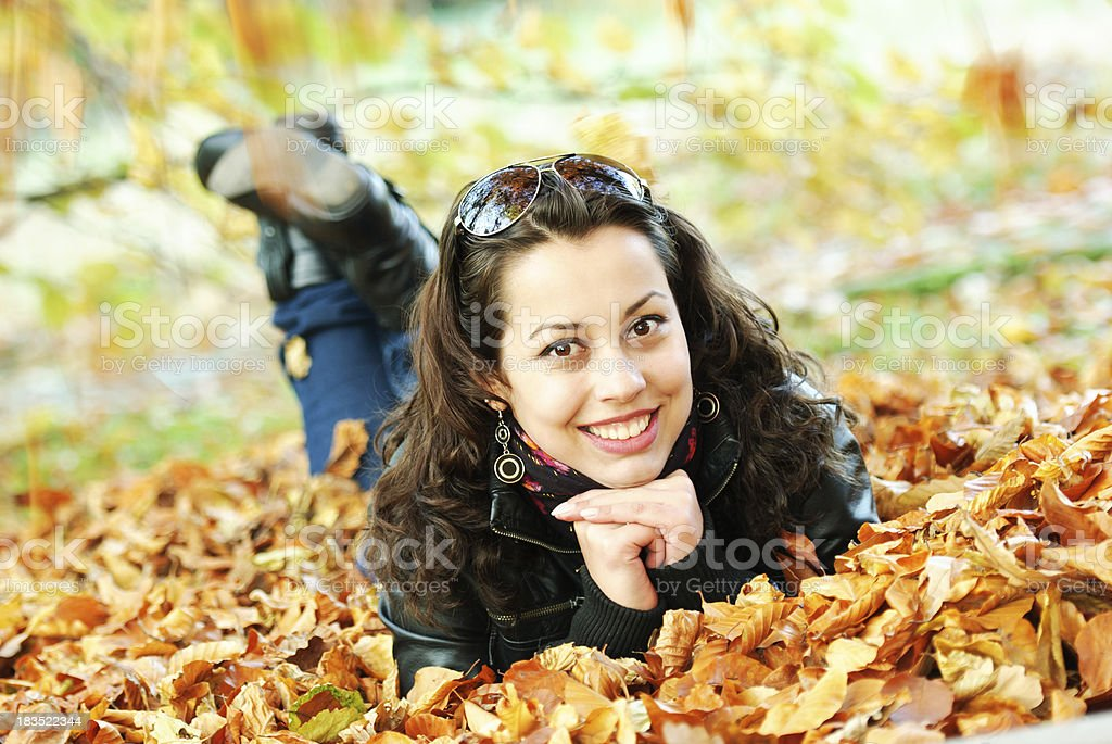 Young woman laying in autumn leafs royalty-free stock photo