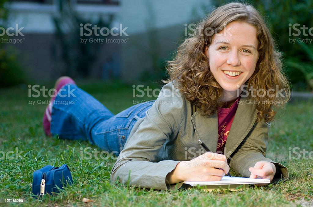 Young woman laying in the grass stock photo