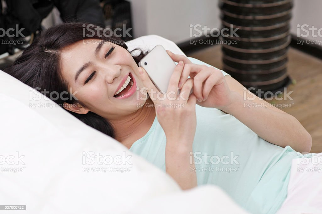 Young woman laying on a couch,holding a cell phone stock photo