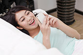 Young woman laying on a couch,holding a cell phone