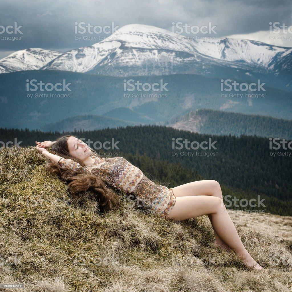 Young woman laying on a hillside in the mountains stock photo