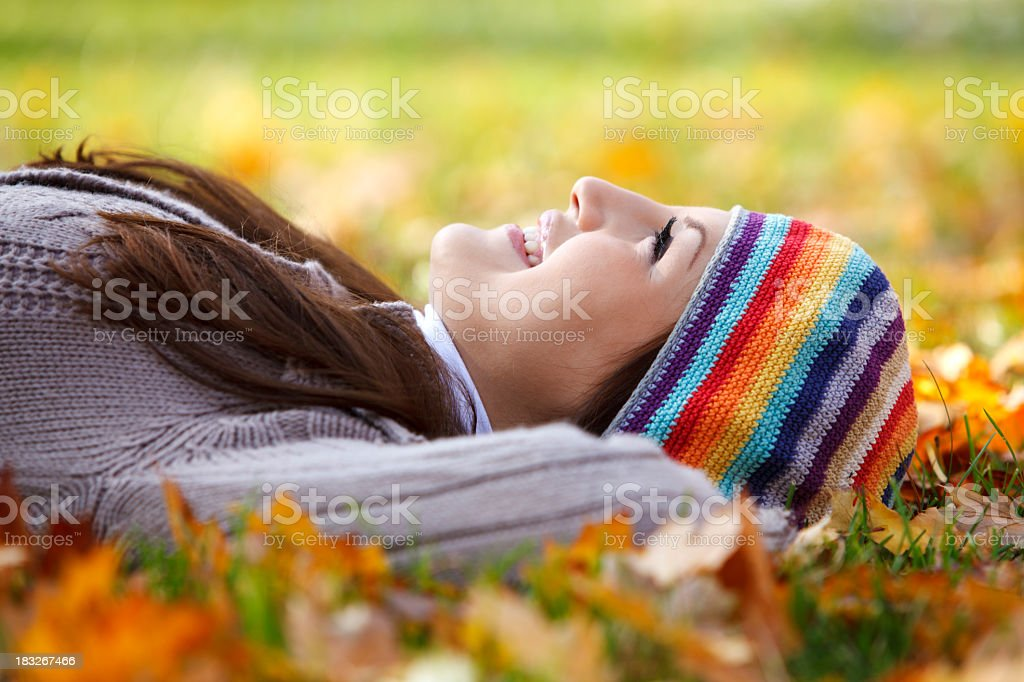 Young woman laying on dry leaves and enjoying life royalty-free stock photo