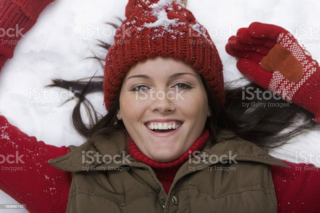 Young woman laying on snow smiling royalty-free stock photo