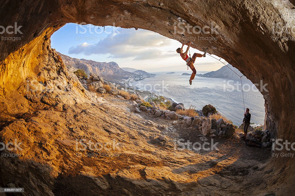 Young woman lead climbing in cave, male climber belaying stock photo