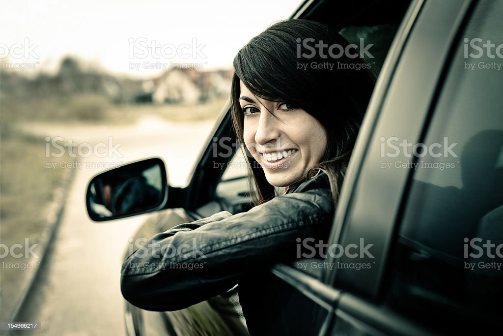 Young woman lean out of car window and looks back royalty-free stock photo