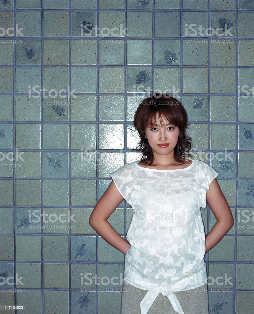 Young woman leaning against tile wall, portrait royalty-free stock photo