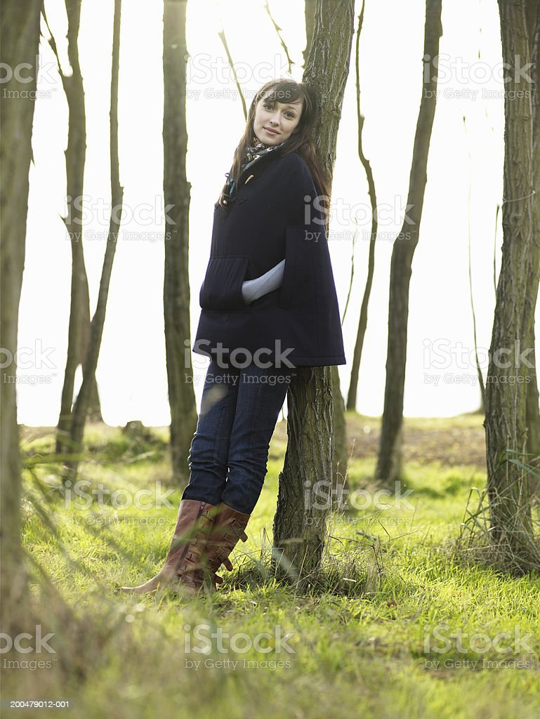 Young woman leaning against tree trunk, autumn, portrait stock photo