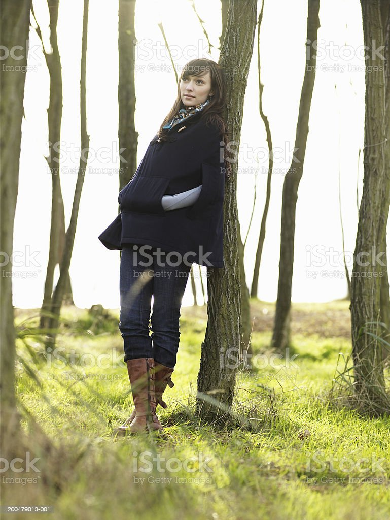 Young woman leaning against tree trunk, looking up, autumn stock photo