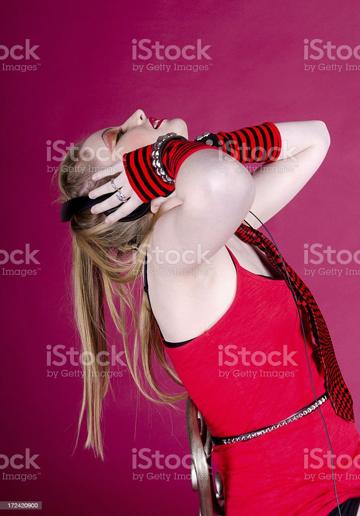 Young woman leaning back in chair, hands on headphones stock photo