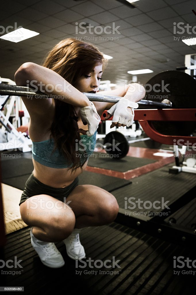 Young woman leaning of a squats rack stock photo