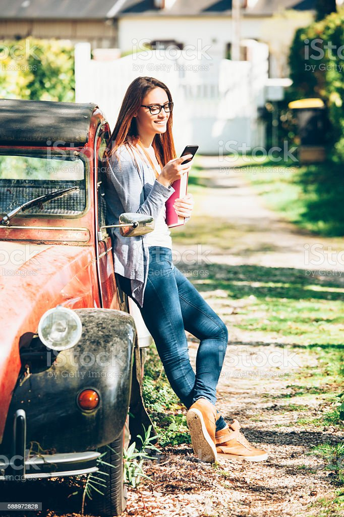 Young woman leaning on a car and using smart phone stock photo