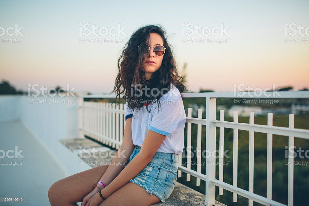 young woman leaning on metal fence on balcony stock photo
