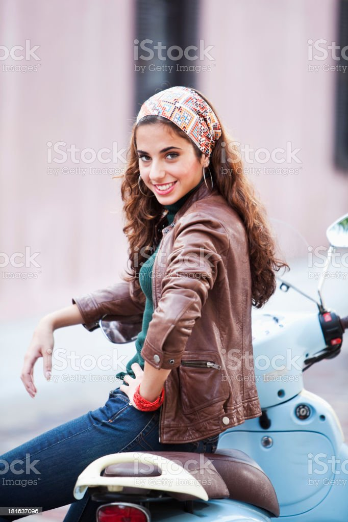 Young woman leaning on motor scooter royalty-free stock photo